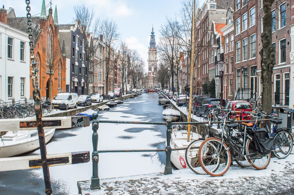 Winter in Amsterdam with a thin layer of snow on the canals