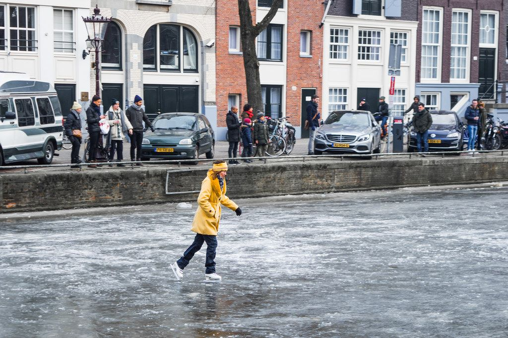 A woman in a yellow coat and headband skates on the Prinsengracht canal