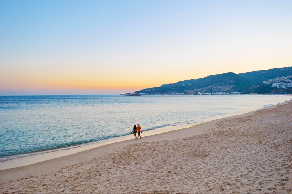 A couple takes a sunset stroll along the Sesimbra beach