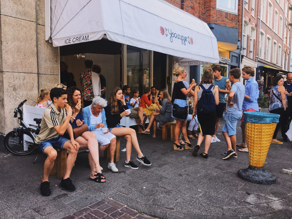 A crowd of people sitting and standing in front of an ice cream shop in Amsterdam.