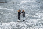 Two girls hold onto each other on a frozen canal
