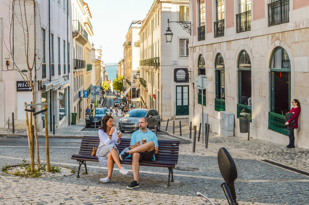 A sunny spring day in Lisbon: a couple leisurely enjoy their ice cream on a bench.