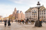 Dam Square in Amsterdam, with a horse and carriage in the background.