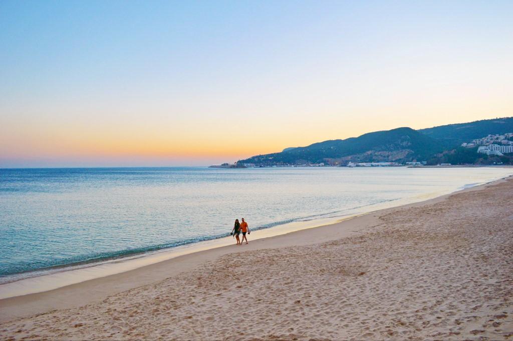 A couple takes a sunset stroll along the Sesimbra beach