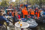 King's Day in Amsterdam, people dressed in orange drinking beer and partying