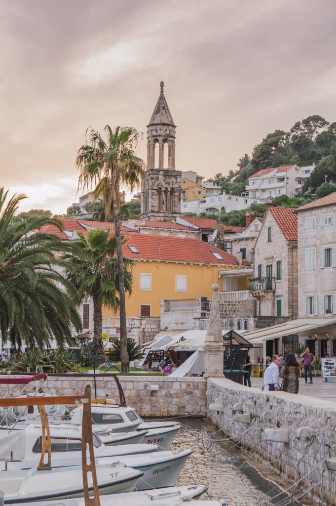 Sunset in Hvar, with the church tower and palm trees in the background