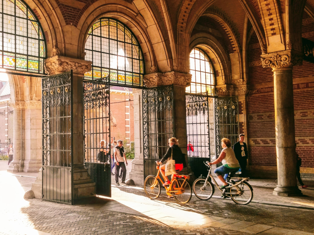 Two women cycle in the shadows of the Rijksmuseum passage.