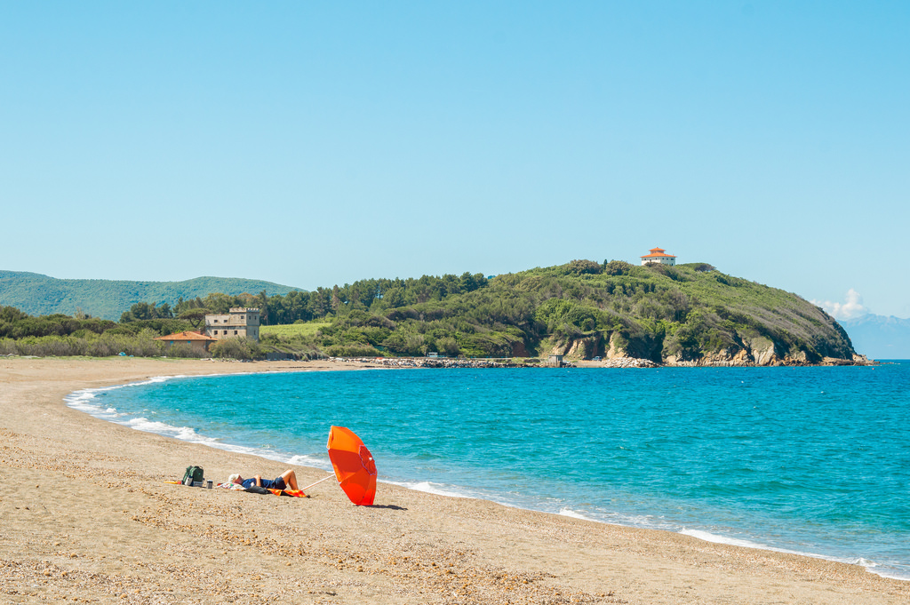 A quiet beach on the Etruscan Coast. A man relaxes underneath an orange parasol.
