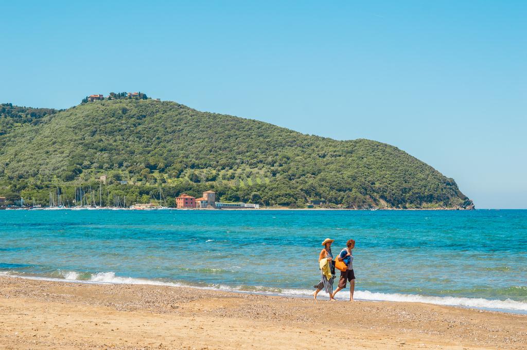 Two women walk on a beach near the Gulf of Baratti