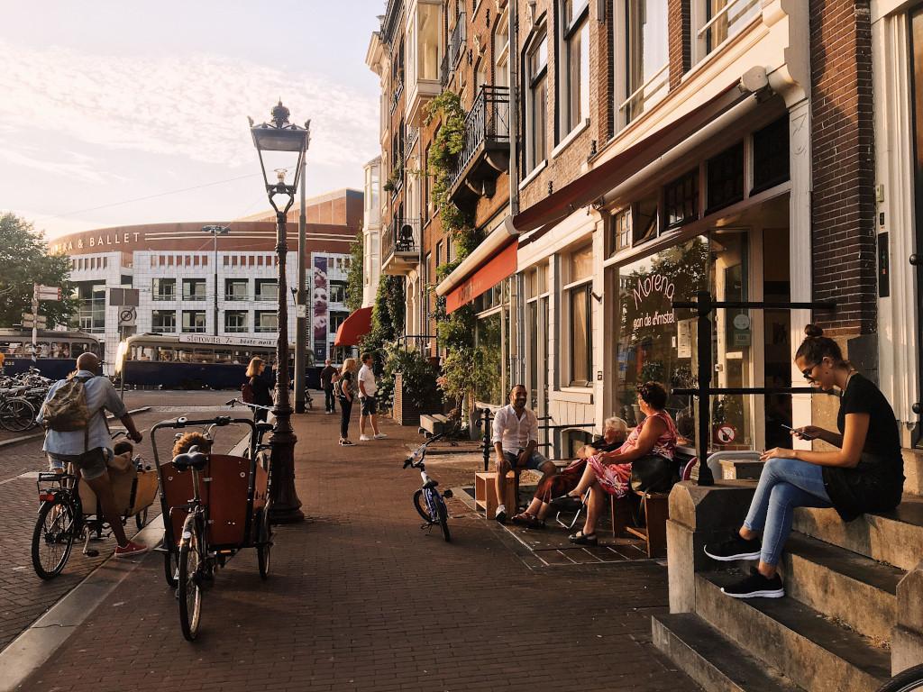 Locals in Amsterdam enjoying the golden hour sunlight in the cooler evening temperatures.