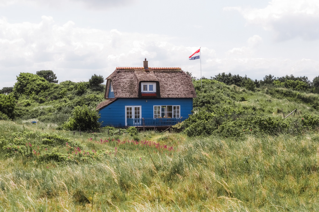 A little blue house with a thatched roof on Ameland, Friesland.