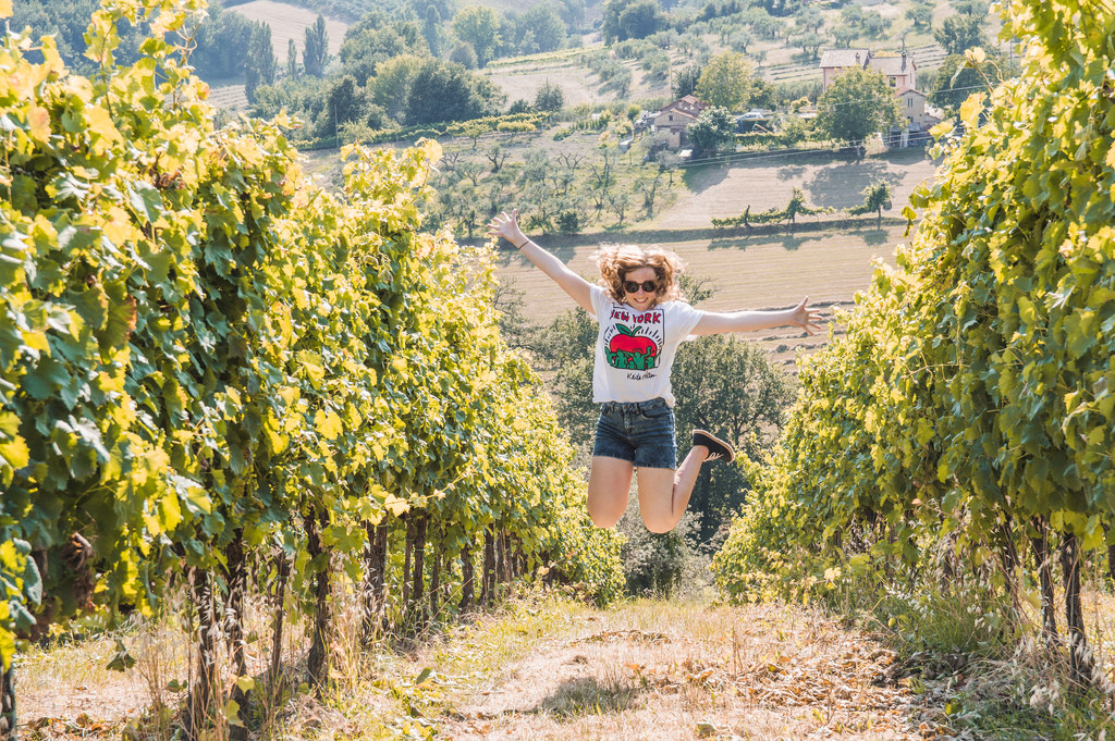Jumping in the air in the vineyards of Montefalco in Umbria