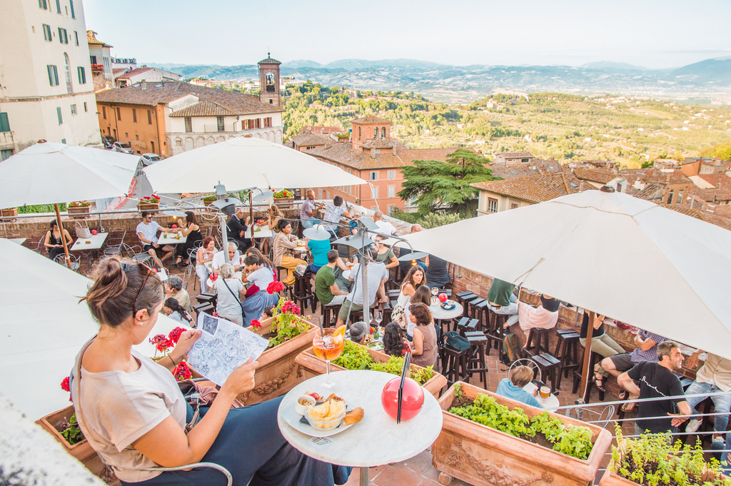 A busy terrace in Perugia looks out on the landscape in Umbria.