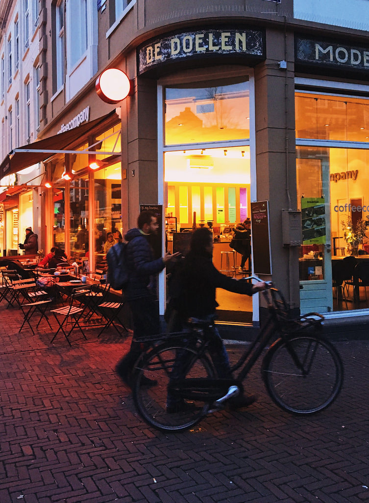 Amsterdam in the evening, two people walk by, one with a bicycle.