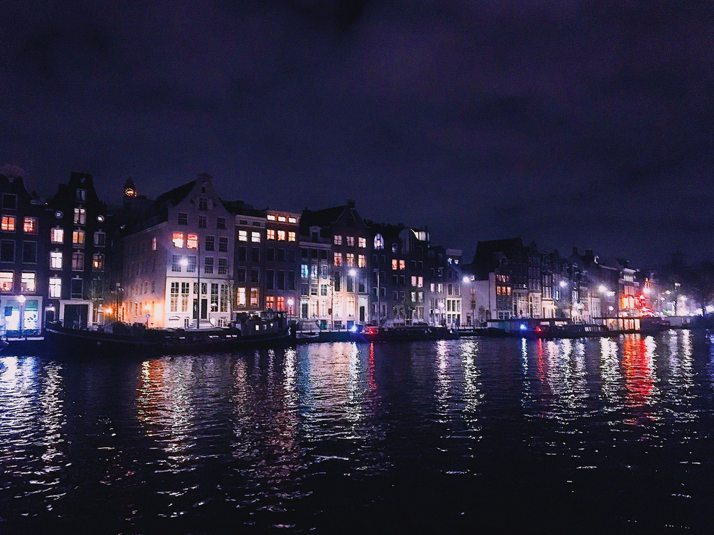 Night time on the Amstel river in Amsterdam.