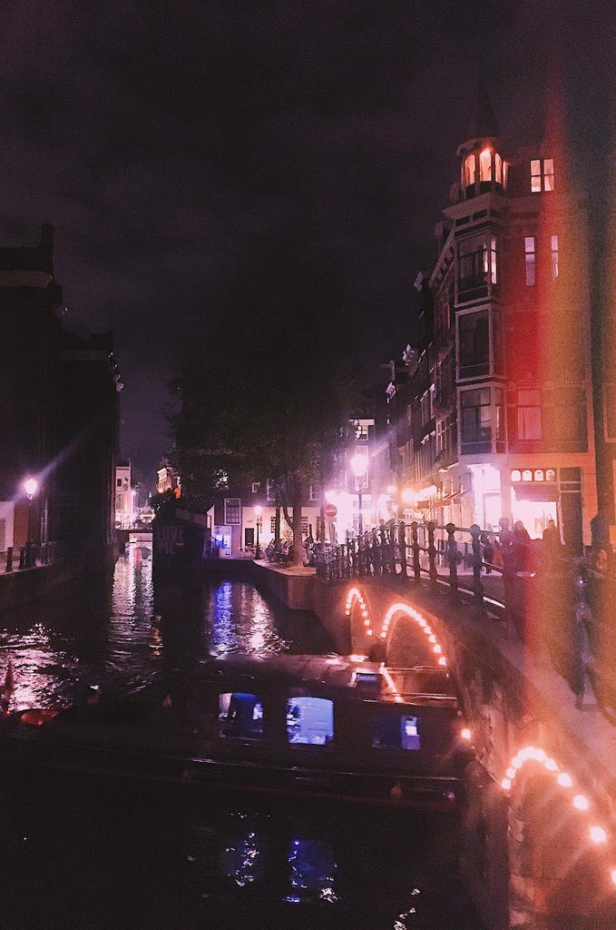 Night lights in historic Amsterdam. A boat passes underneath a bridge.