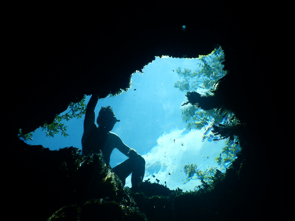 A diver in the underwater opening of a cave