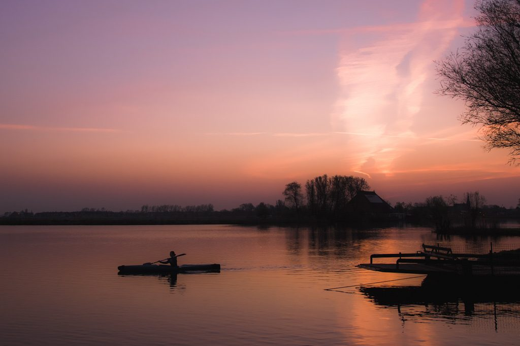 Canoeing on a still lake while the sun rises with pinks and purples in the sky.