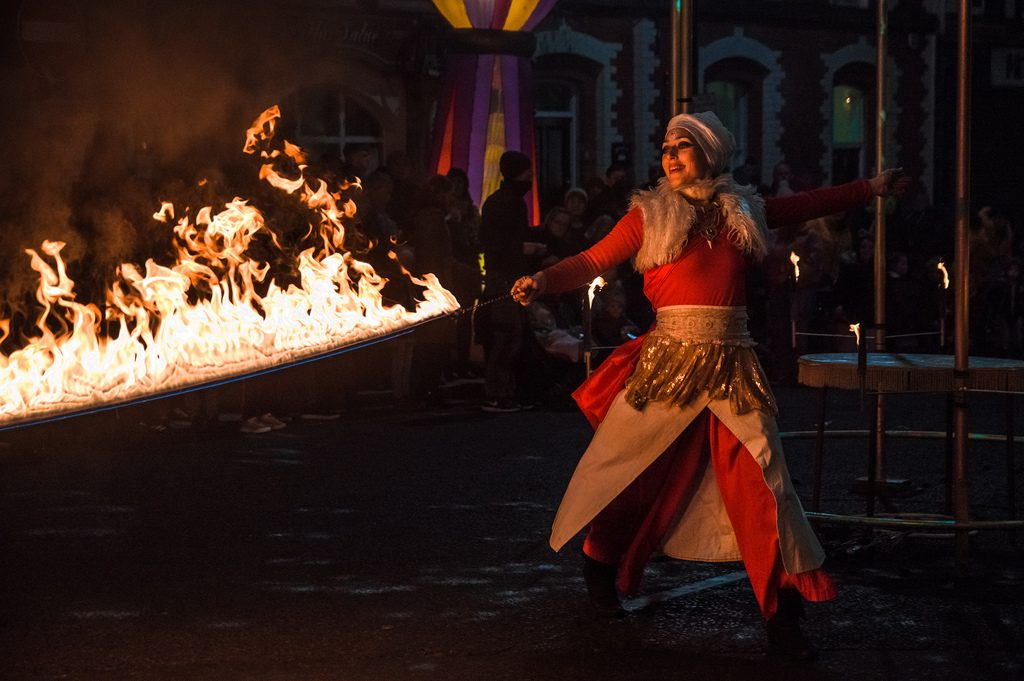 A dancer in costume performs a fire dance.