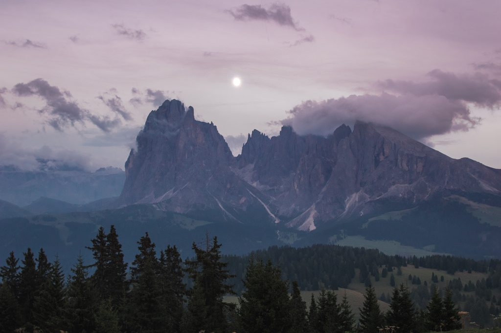 The moon rises over the mountains in the Dolomites, with a pruple-toned sky and a few clouds.