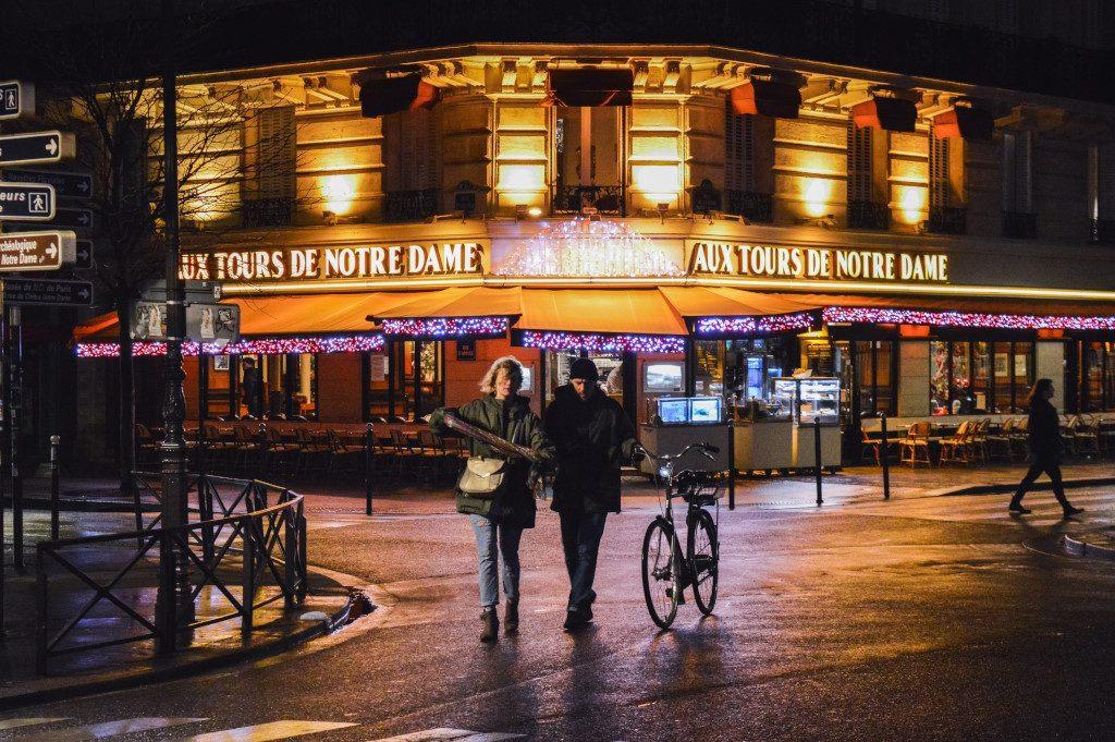 A couple walks on the streets of Paris by night, with a bicycle in hand.