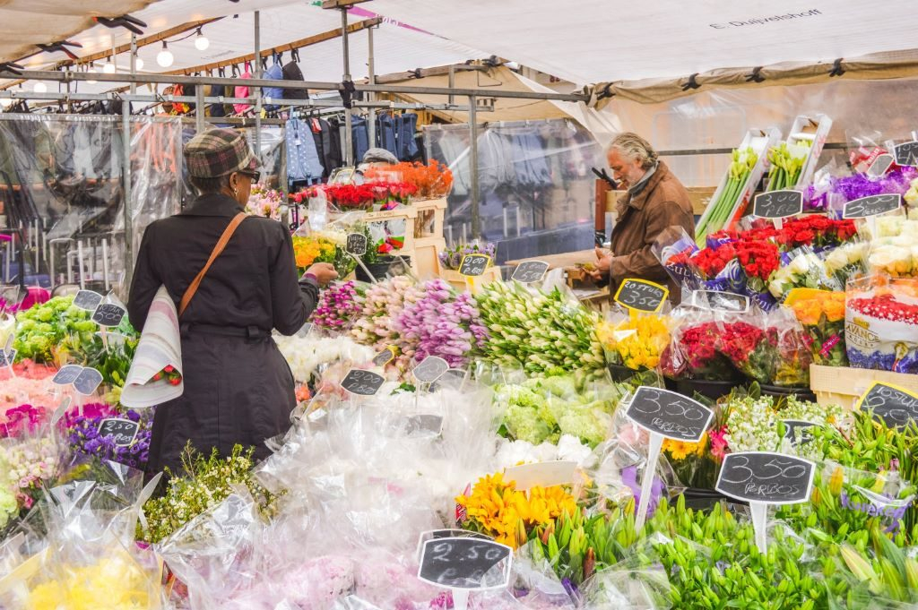 A woman buys flowers from a vendor at the Albert Cuyp market