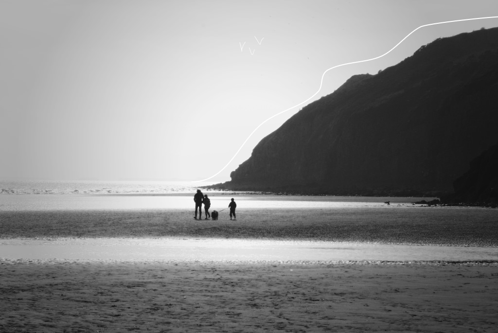 Black and white photo of a family walking their dog on Pendine Sands beach