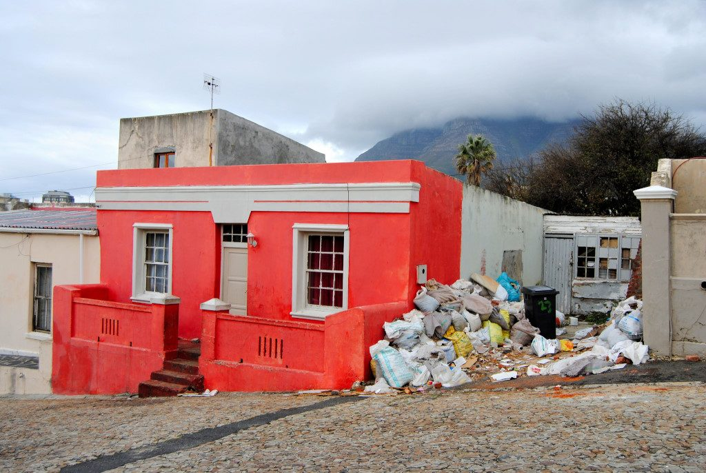 A bright red house and a pile of trash