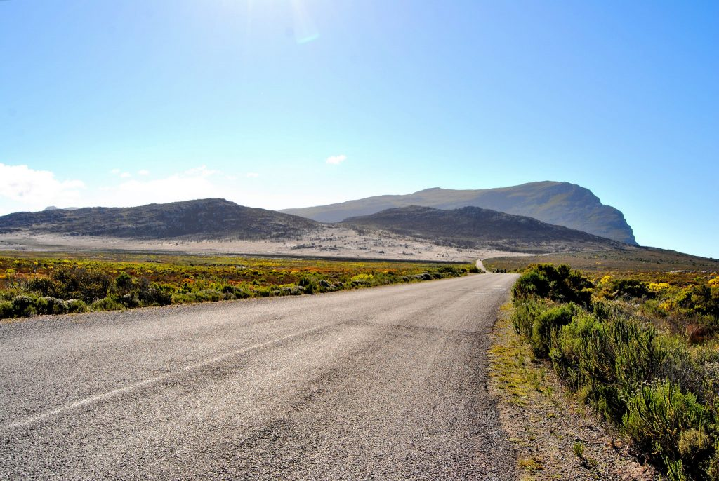 Cycling on the Cape Peninsula in South Africa (a long empty road with mountains in the background)