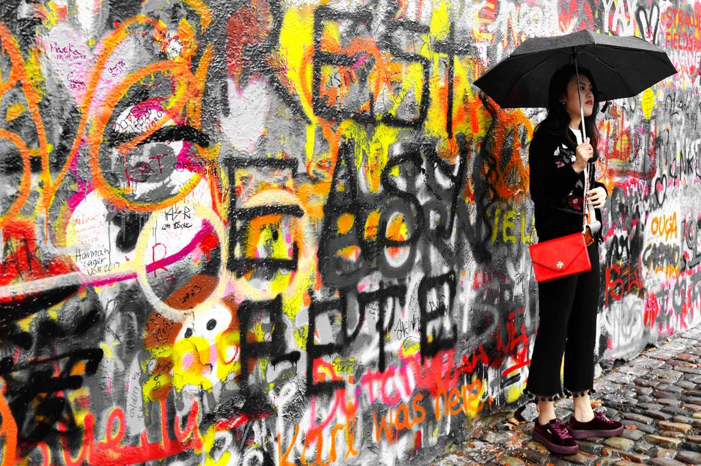 A woman poses in front of the Lennon Wall with an umbrella