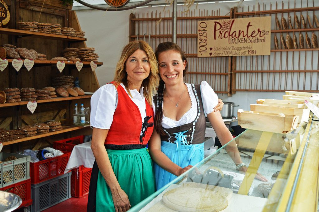 Two local women in South Tyrol, dressed in traditional clothing and seling bread at the market square in Brixen.