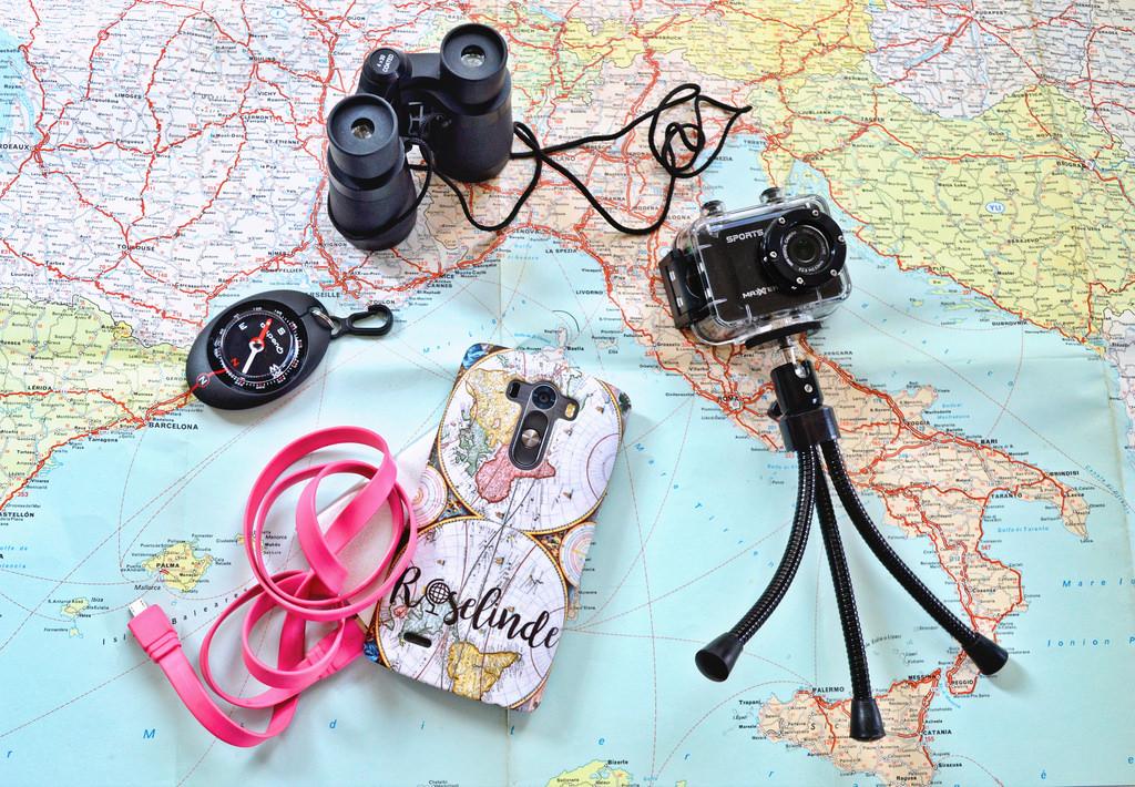 An overview of my travelgadgets: binoculars, compass, phonecase, mini camera