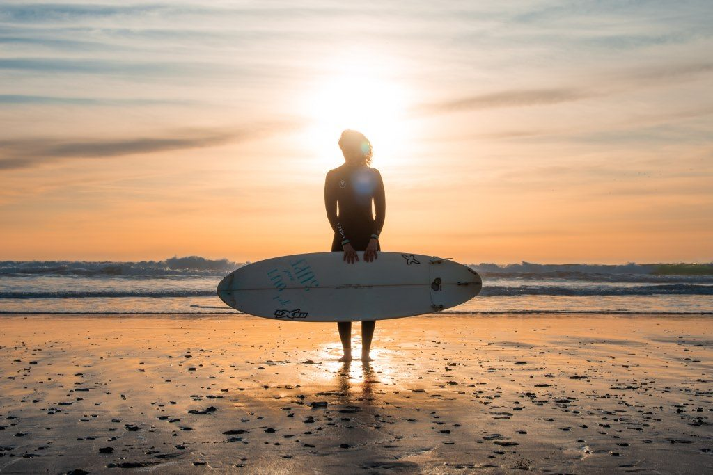 Isabelle (silhouette) poses in front of the sunset with her surfboard.