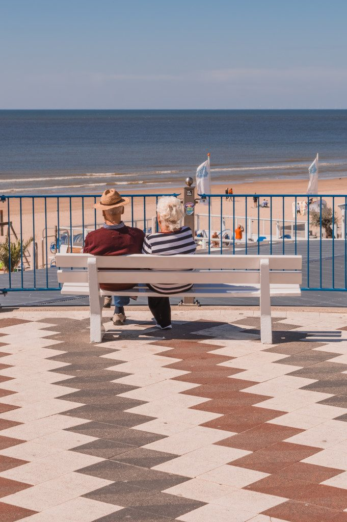 An elderly couple enjoying the view of the sea from a bench near the beach.