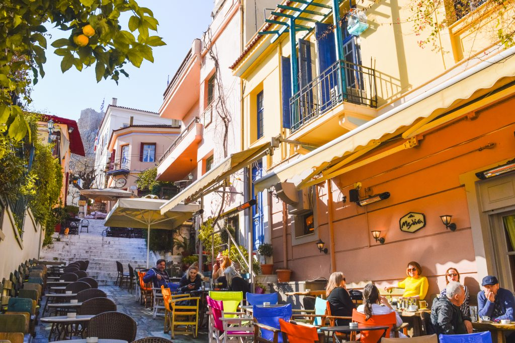 The historic Plaka neighbourhood in Athens with people relaxing on terraces in the sun