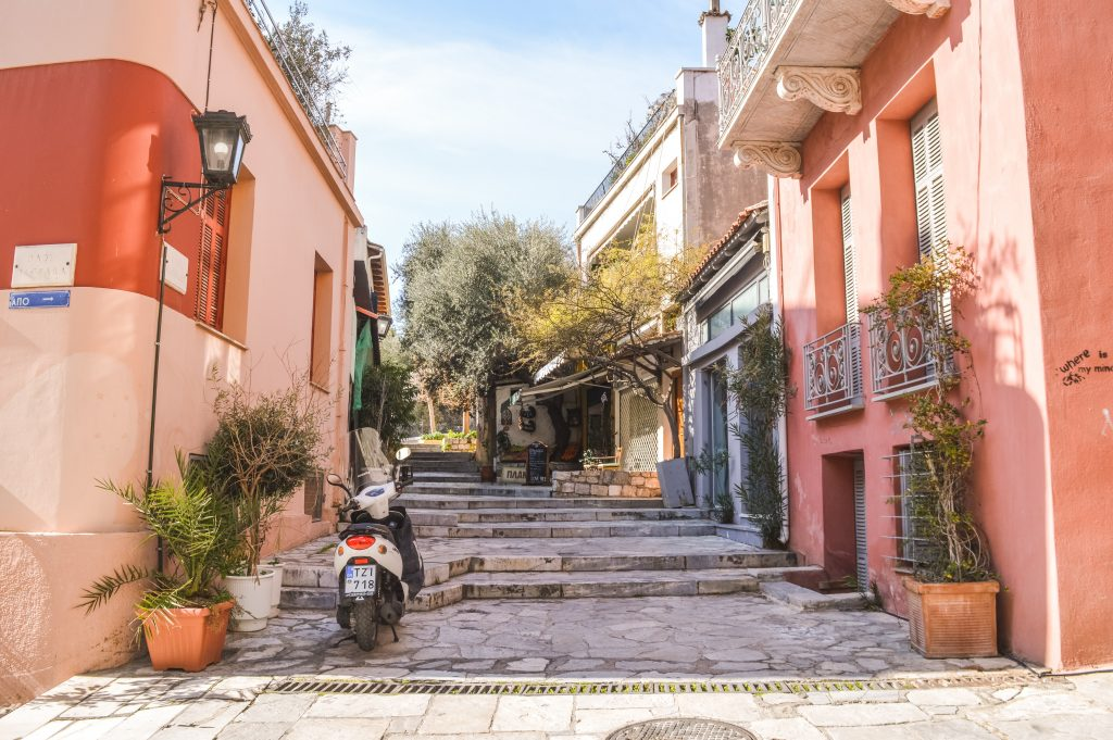 A quiet street with pink walls and green plants in the historic Plaka neighbourhood in Athens