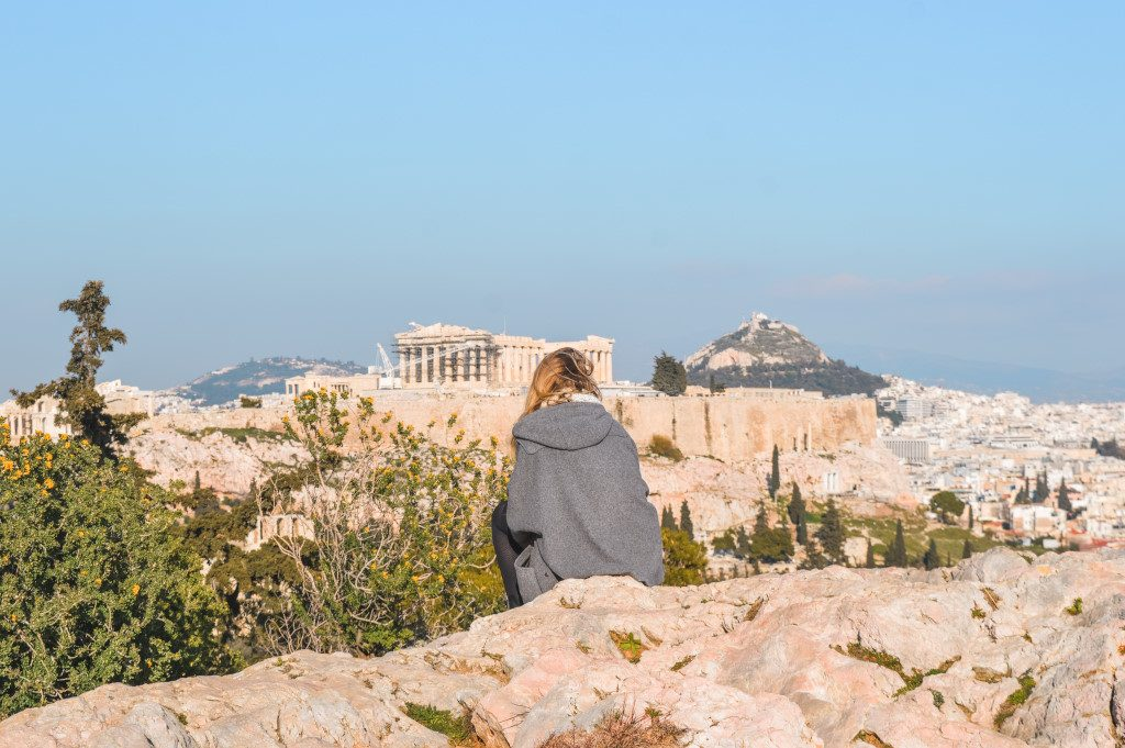 A girl in a grey coat admires the view of the Acropolis from Filopappou Hill.