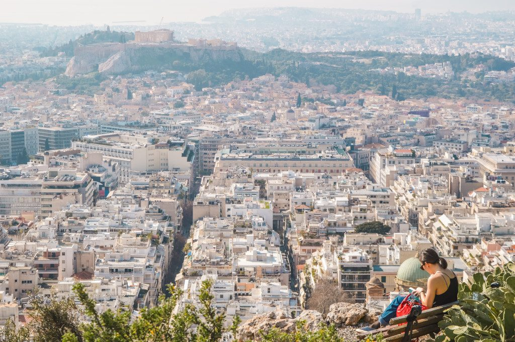 The view of the city and Acropolis in the distance from Mount Lycabettus. A girl is reading a book in the forefront.