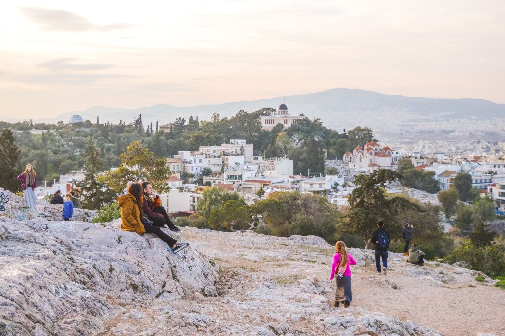 Groups of people enjoy the sunset at Areopagus or 'Mars Hill' in Athens