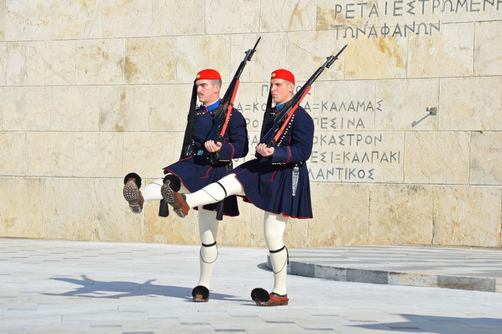 Two guards in traditional dress put one leg forward as they perform the changing of the guards in Athens