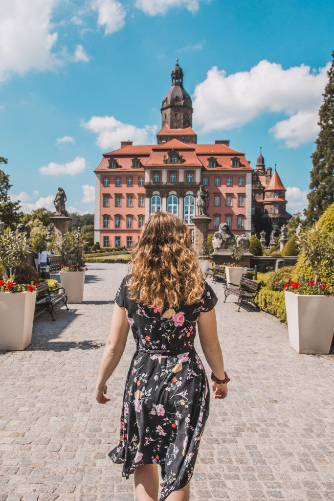Roselinde, wearing a floral dress, walks towards castle Ksiaz in the background (a major highlight in Lower Silesia, Poland)