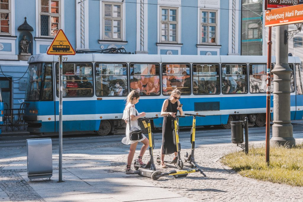 Two young women using scooters to get around town in Wroclaw