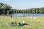 The Grote Vijver in the Amsterdamse Bos. A man is reading a book in the grass and others are swimming.