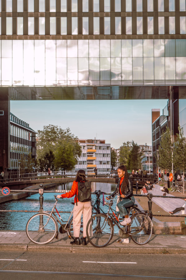 Bridge in Amsterdam with two young women chatting with their bicycles in hand