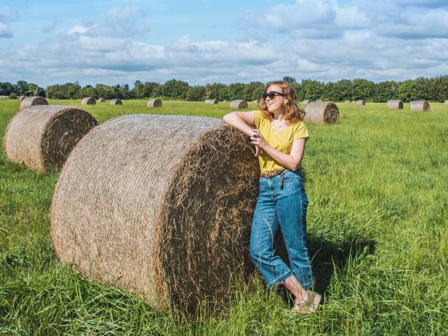 Roselinde poses with a bale of hay in Normandy, France