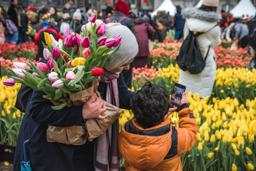 A mother carrying tulips looks at a smartphone her son is holding