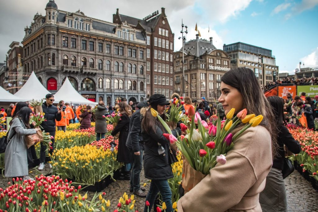 A young woman poses with a bunch of tulips on National Tulip Day in Amsterdam (2020)
