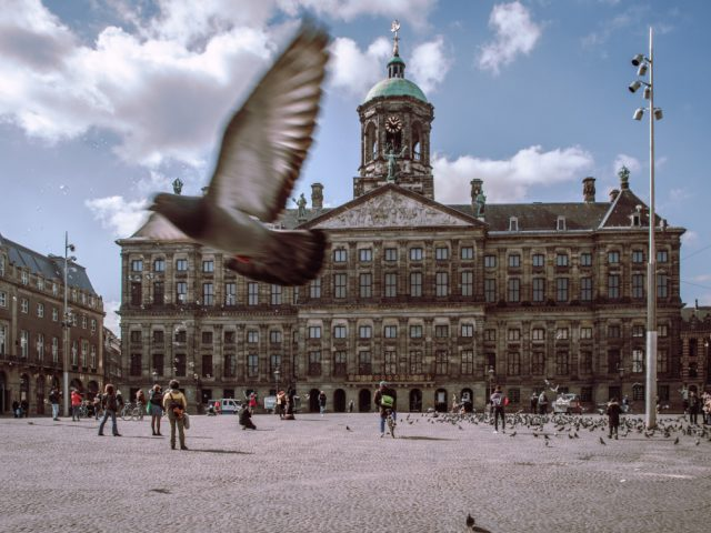 A pigeon flies by on a noticeably quiet Dam Square while Amsterdam is in semi-lockdown for the coronavirus.