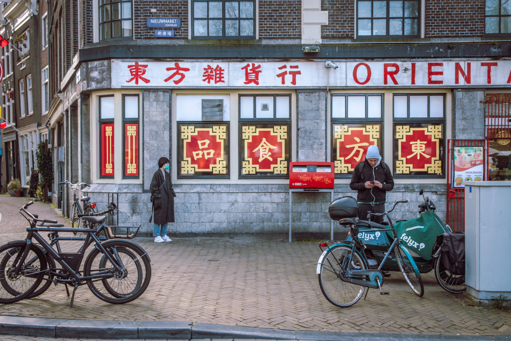Quiet China Town in Amsterdam during the corona virus lockdown, a woman is wearing a face mask